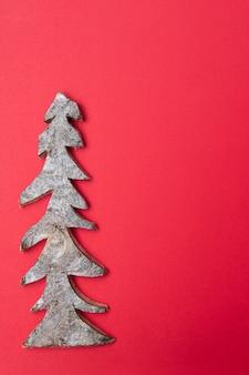 Drewniana choinka na czerwonym tle. kartka świąteczna.