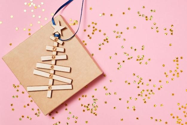 Drewniana choinka na pudełku prezentowym na niebieskim różowym brokatowym tle
