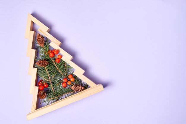 Drewniana choinka z gałęziami jodły w środku ozdobiona jagodami jarzębiny z miejscem na kopię