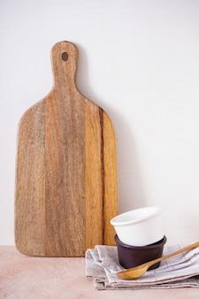 Drewniana deska do krojenia i naczynia kuchenne na beżowym stole, zbliżenie.