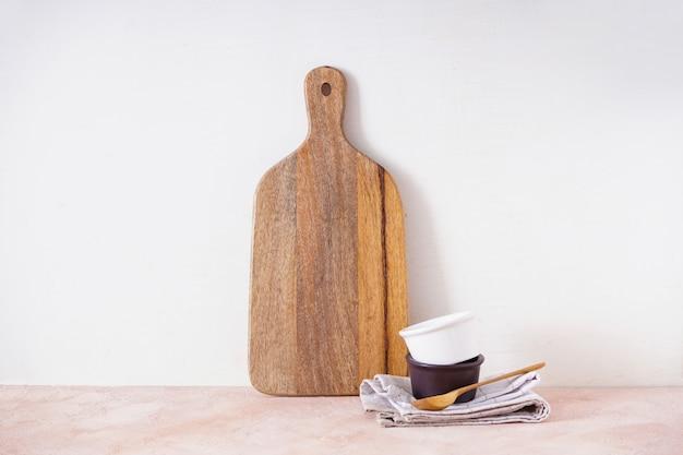 Drewniana deska do krojenia i naczynia kuchenne na beżowym tle. miejsce na tekst