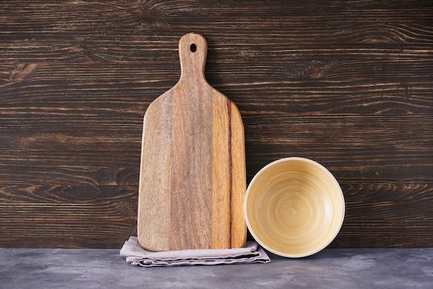 Drewniana deska do krojenia i naczynia kuchenne na tle drewnianych, miejsce na tekst.