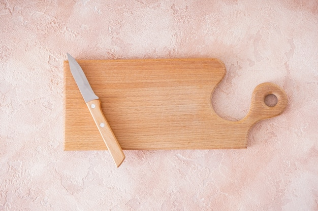 Drewniana deska do krojenia i nóż na beżowym tle, miejsce na tekst. widok z góry.