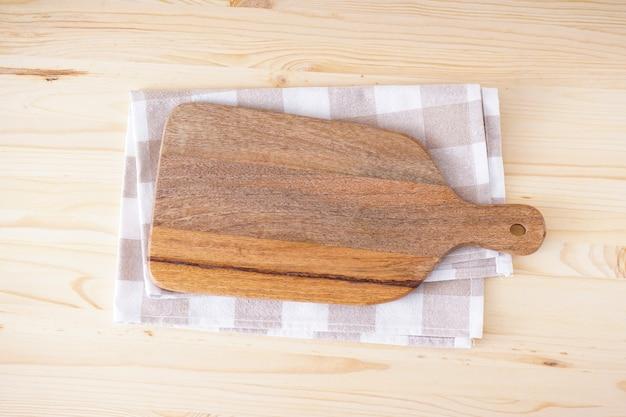Drewniana deska do krojenia i ręcznik kuchenny na drewnianym stole, miejsce na tekst. leżał na płasko.