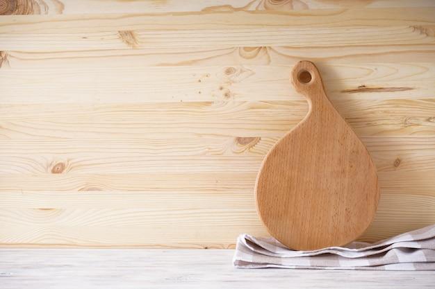 Drewniana deska do krojenia i ręcznik kuchenny na tle drewnianych, miejsce na tekst.