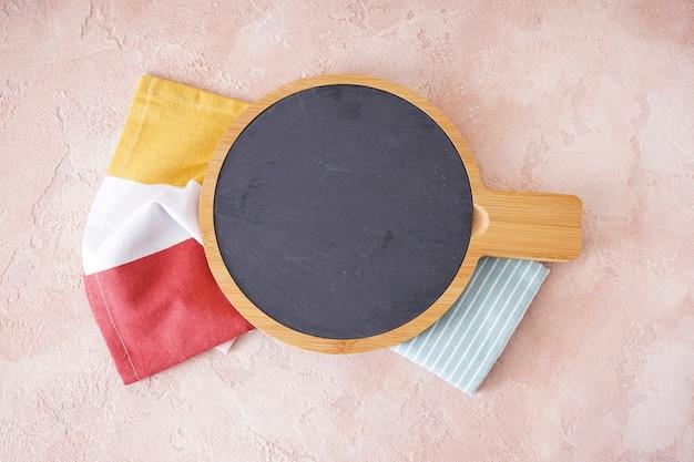 Drewniana deska do krojenia i ręcznik na beżowym tle, miejsca na tekst. leżał na płasko.