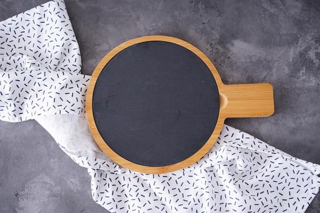 Drewniana deska do krojenia i ręcznik na szarym tle, miejsca na tekst. leżał na płasko.