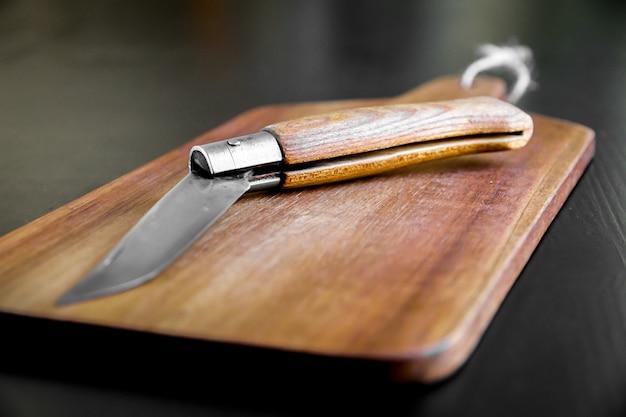 Drewniana deska do krojenia i scyzoryk na czarnym stole w kuchni