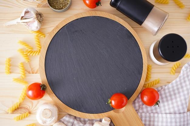 Drewniana deska do krojenia i świeże składniki do gotowania: makaron, pomidor i przyprawy na drewnianym stole, widok z góry.