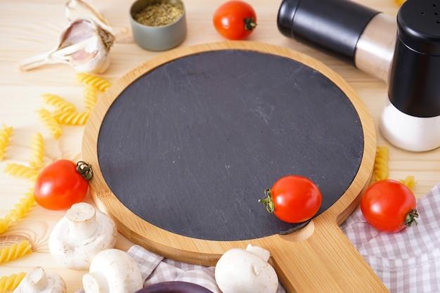 Drewniana deska do krojenia i świeże składniki do gotowania: makaron, pomidor i przyprawy na drewnianym stole. zbliżenie