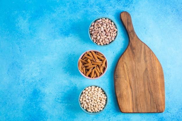 Drewniana deska do krojenia i trzy miski pełne surowego makaronu i fasoli na szarej powierzchni.