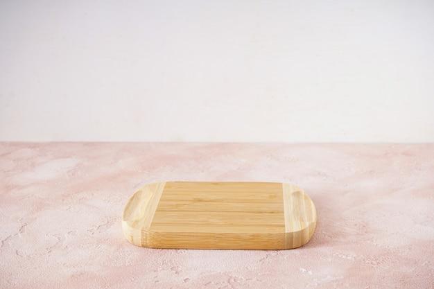 Drewniana deska do krojenia na beżowym tle z miejscem na tekst.