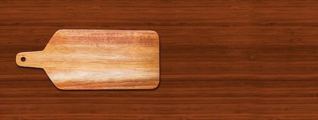 Drewniana deska do krojenia na białym tle na ciemnym tle drewna. poziomy baner panoramiczny