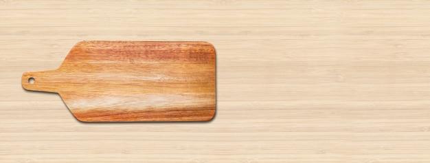Drewniana deska do krojenia na białym tle na tle drewna. poziomy baner panoramiczny
