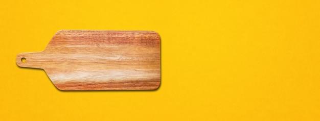 Drewniana deska do krojenia na białym tle na żółtym tle. baner poziomy