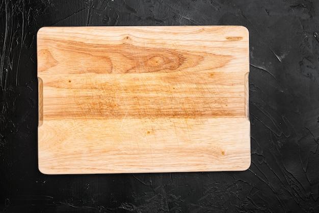 Drewniana deska do krojenia, na czarnym tle ciemnego kamiennego stołu, widok z góry na płasko, z miejscem na kopię tekstu lub produktu