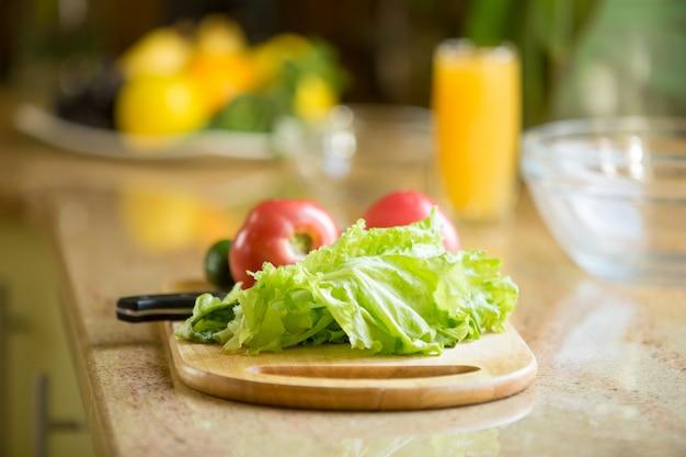 Drewniana deska do krojenia na stole ze świeżymi warzywami na