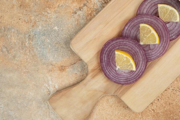 Drewniana deska do krojenia pokrojonej w plasterki cebuli i cytryny na marmurowej powierzchni