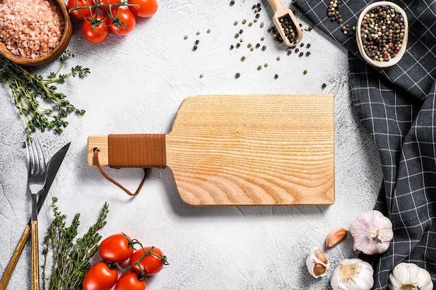 Drewniana deska do krojenia w centrum świeżych surowych warzyw, warzyw. zdrowe, czyste jedzenie, wegańskie, dietetyczne pojęcie żywności. widok z góry. skopiuj miejsce