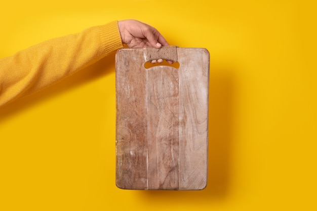 Drewniana deska do krojenia w ręku na żółto