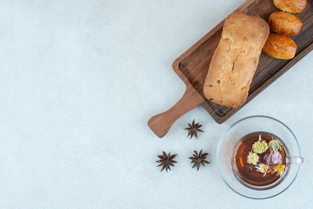 Drewniana deska do krojenia z ciastem i herbatą ziołową