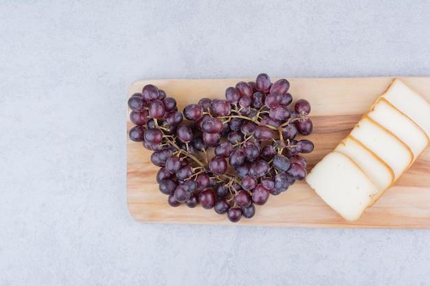 Drewniana deska do krojenia z krojonym chlebem i winogronami. zdjęcie wysokiej jakości