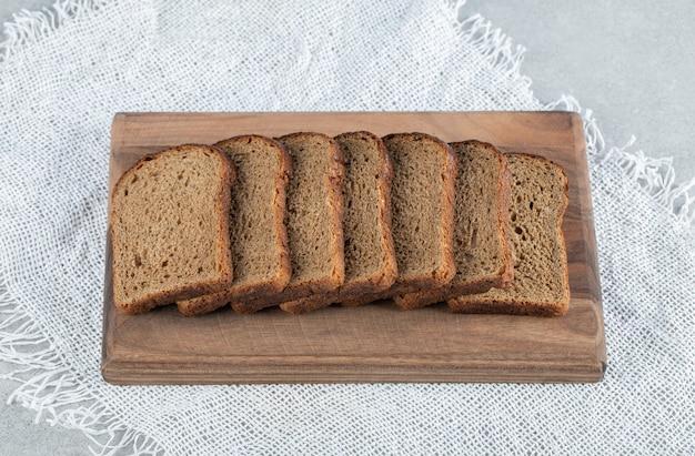 Drewniana deska do krojenia z kromkami ciemnego chleba.