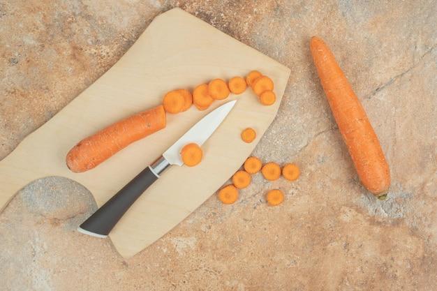 Drewniana deska do krojenia z pokrojoną marchewką i nożem