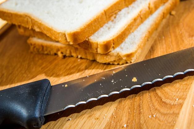 Drewniana deska do krojenia z pokrojonym białym chlebem i nożem na drewnianym stole