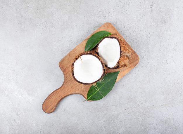 Drewniana deska do krojenia z pokrojonym kokosem i liśćmi. wysokiej jakości zdjęcie
