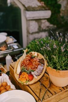 Drewniana deska do krojenia z prosciutto z serem i suszonymi morelami na pudełku z doniczką