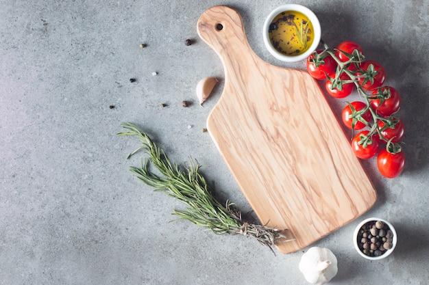 Drewniana deska do krojenia ze świeżych ziół i surowych warzyw na stole rustykalnym drewna. widok z góry. gotowanie w tle.