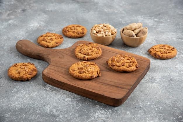 Drewniana deska domowych ciasteczek z organicznych orzeszków ziemnych na marmurowym stole.