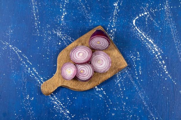 Drewniana deska fioletowych krążków cebuli na marmurowym stole.