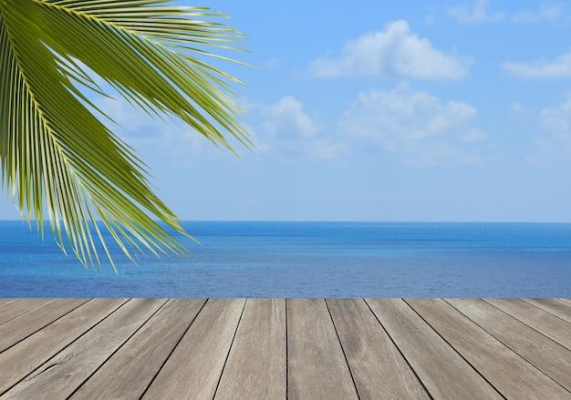 Drewniana deska nad plażą z liściem palmy kokosowej