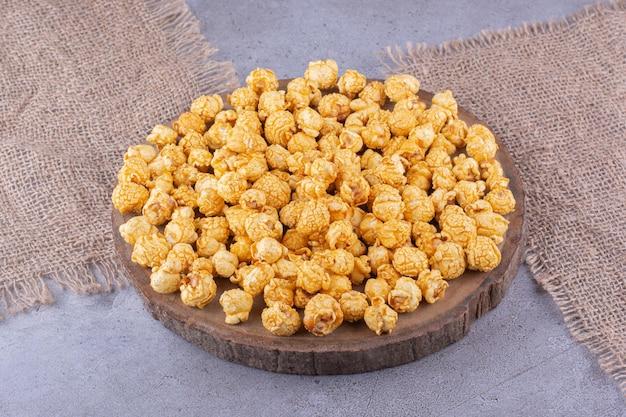 Drewniana deska pełna cukierków popcornu i dwóch kawałków tkaniny na marmurowym tle. zdjęcie wysokiej jakości