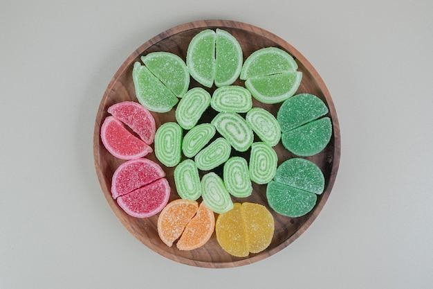 Drewniana deska pełna kolorowych, cukierkowych marmolad.