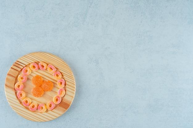 Drewniana deska pełna okrągłych pomarańczowych cukierków galaretkowych w kształcie kółek i pomarańczowych galaretek z cukrem