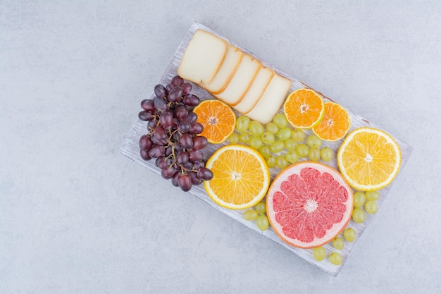 Drewniana deska pełna pokrojonych owoców i chleba. zdjęcie wysokiej jakości