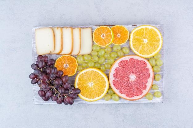 Drewniana deska pełna pokrojonych owoców i chleba