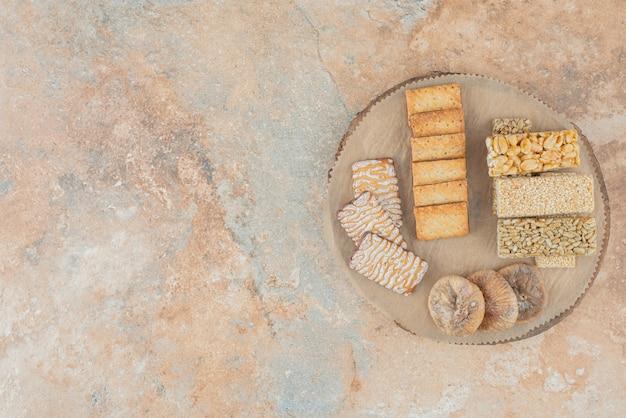 Drewniana deska pełna słodkich ciasteczek i kawałków orzechów ziemnych