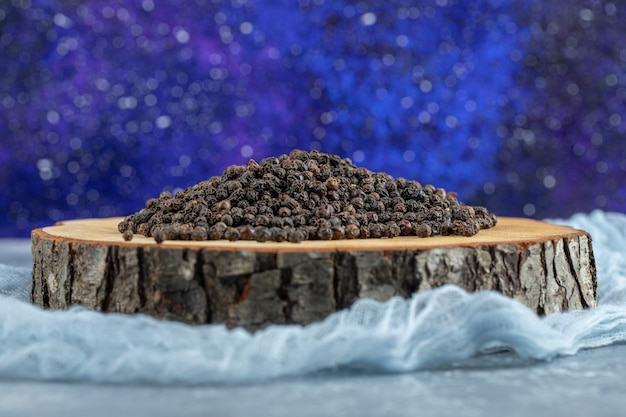 Drewniana deska pełna suszonych ziaren pieprzu.
