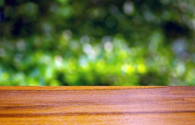 Drewniana deska pusty stół przed zielonym tłem bokeh do wyświetlania produktu