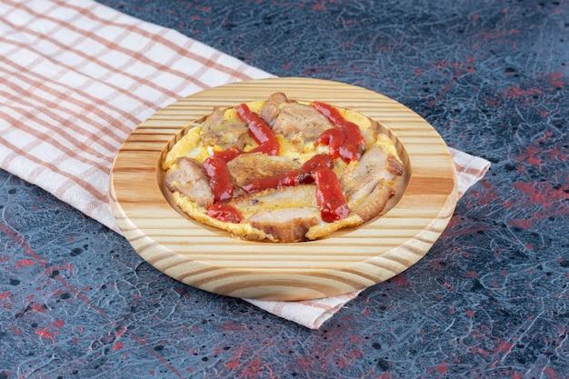 Drewniana deska pysznego jajka sadzonego z mięsem i sosem pomidorowym.