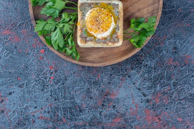 Drewniana deska pysznych tostów z mięsem i warzywami.