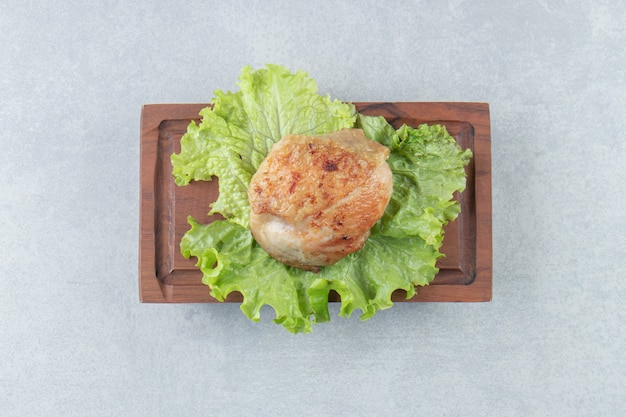 Drewniana deska smażonego mięsa z kurczaka z sałatą.