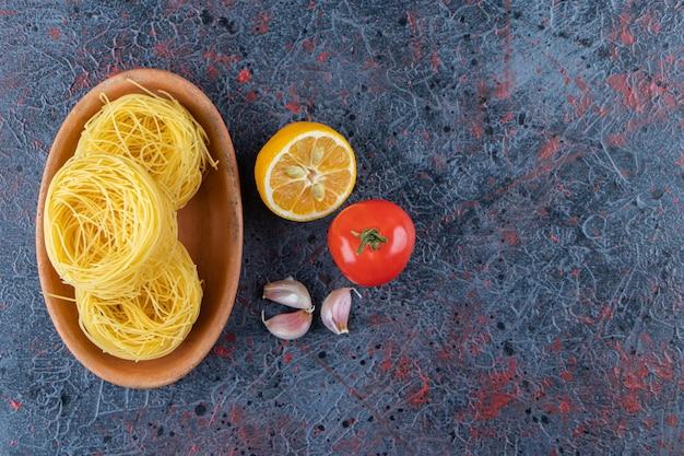 Drewniana deska surowego suchego makaronu gniazdowego z cytryną i świeżym czerwonym pomidorem na ciemnym tle.
