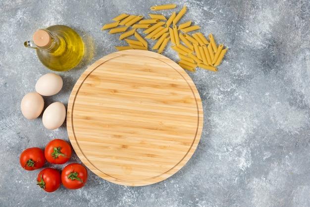 Drewniana deska surowego, suchego spaghetti, jajek i pomidorów na marmurowej powierzchni.