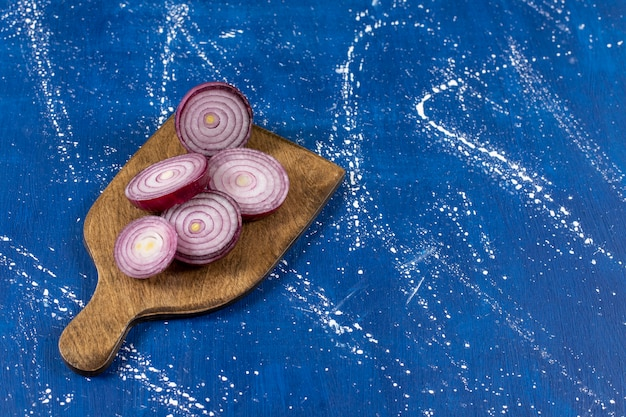 Drewniana deska z fioletowymi krążkami cebuli na marmurowej powierzchni