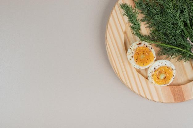 Drewniana deska z gotowanym jajkiem z przyprawami i zieleniną.